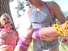 A Brutal Bondage Scene Outdoors With..