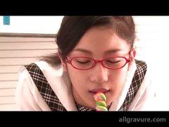 Schoolgirl in glasses licks a lollipop