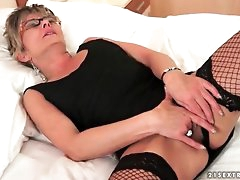 Solo old lady in glasses and fishnets masturbates