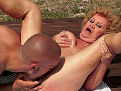 Slutty granny gets her bushy pussy licked and fucked by the pool