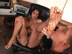 Brunette in fishnet gives a good footjob