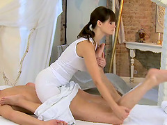 Cute brunette masseuse gives a footjob..