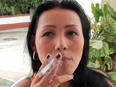 Beautiful girl smokes in close up