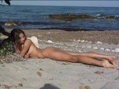 Erotic nude tease on sandy beach