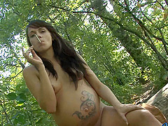 Pregnant tattooed brunette smokes a..