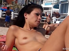 Babe smoking on the beach has small tits