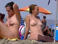 Nice women sunbathing on beach in..