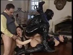 Ass fisting in a latex orgy