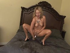 Blonde makes a mess squirting on the bed